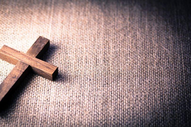 Imagem de uma cruz sobre um tecido de juta. Ela representa a oração do perdão.