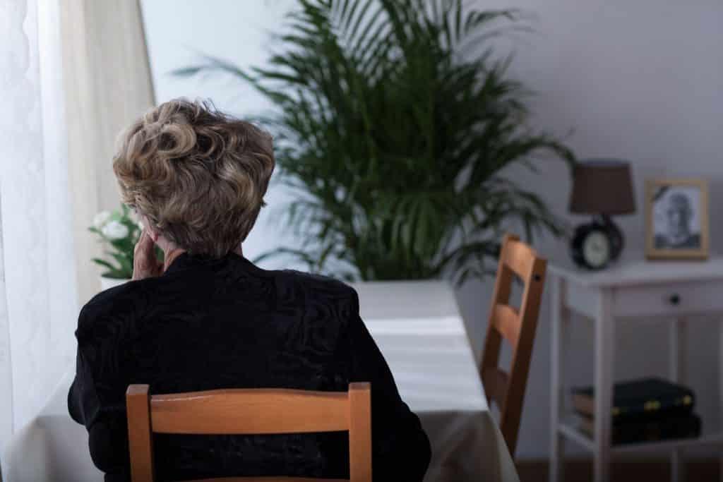 Senhora sentada na mesa de jantar de costas olhando para o lado pensativa