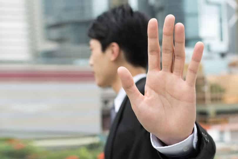 Homem na rua de roupas sociais estendendo a mão aberta como sinal de recusa.