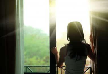 Mulher de costas abrindo a janela de sua sacada pela manhã.