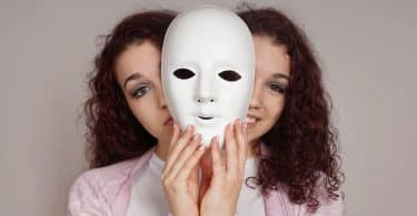 Mulher com máscara em frente ao rosto e expressão de triste e feliz atrás