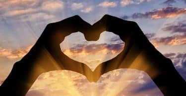 Silhueta de duas mãos fazendo o formado de um coração em frente ao pôr do sol.