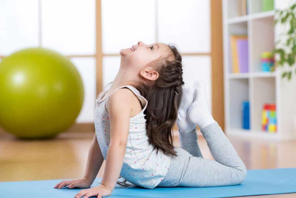 Criança fazendo yoga na sala de casa.