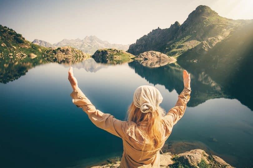 Mulher sentada numa pedra com braços abertos olhando o horizonte