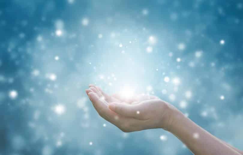 Imagem de uma mão com a palma para cima. A imagem possui um fundo azul claro e pontos de luz e está relacionada à oração do perdão.