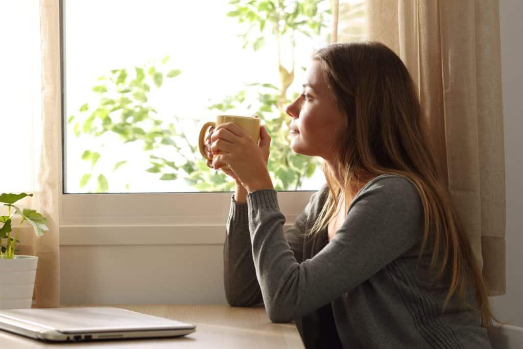 Mulher olhando para fora da janela segurando caneca de café