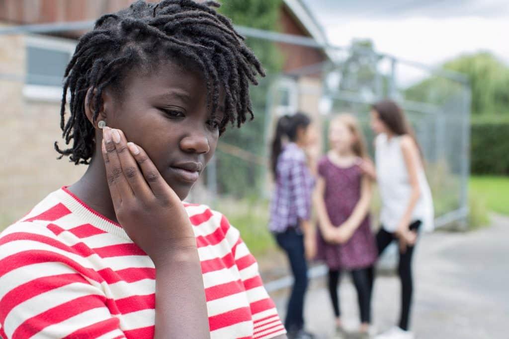Menina negra vista de perfil, triste, enquanto outras meninas brancas estão reunidas atrás, rindo.