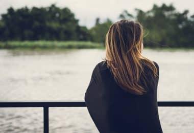Mulher olhando para o rio sozinha