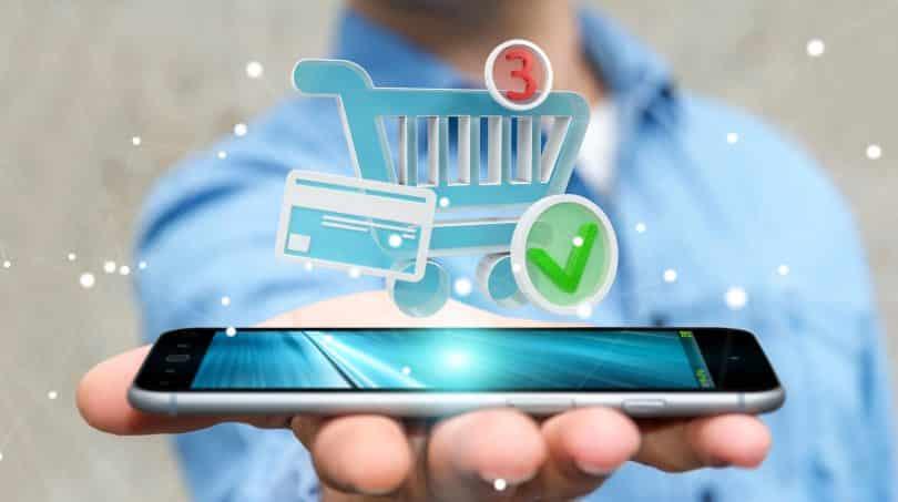 Ilustração de um homem segurando um celular com imagens de compras online flutuando sobre ele.