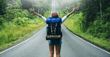 Mulher de costas com braços abertos e estrada em frente