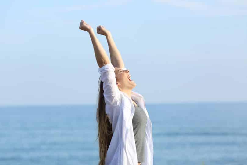 Mulher com os braços para cima em frente ao mar, sorrindo.