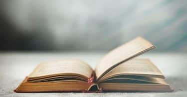 Livro antigo aberto em fundo cinza