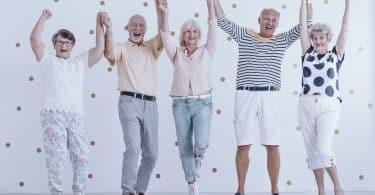 Grupo de cinco idosos sorrindo com as mãos para cima.