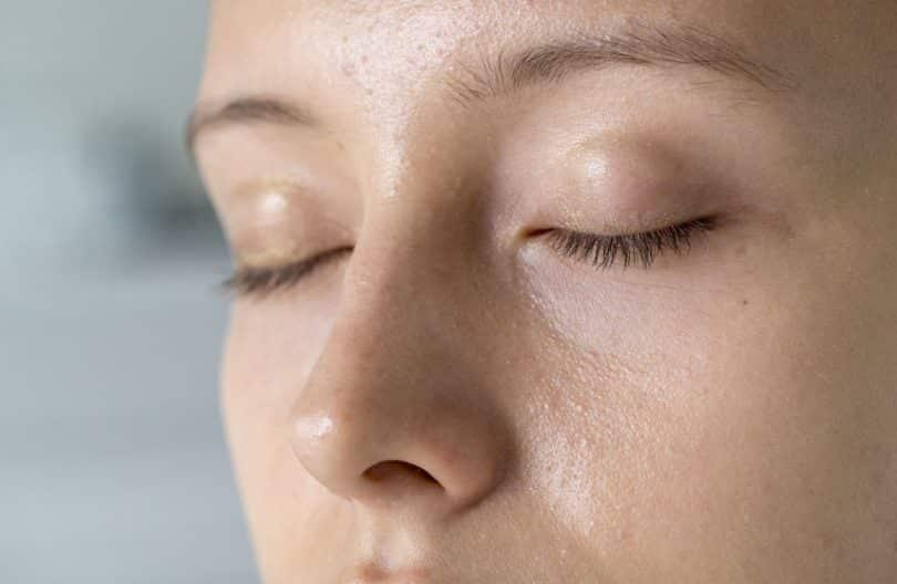Rosto de mulher visto de perto com olhos fechados