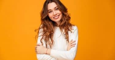 Mulher de cabelos ondulados sorrindo, com os braços cruzados.