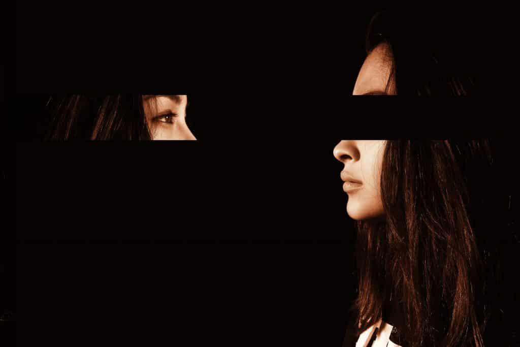 Mulher branca com parte dos olhos recortadas e colocada a frente, olhando para si mesma.