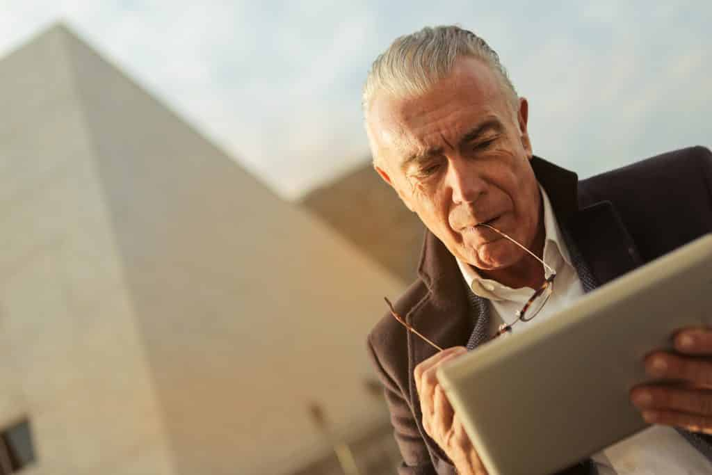 Idoso branco om tablet na mão e óculos na boca ao ar livre