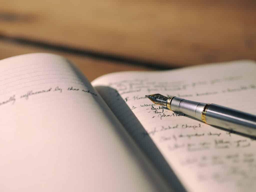 Caderno aberto com uma caneta em cima