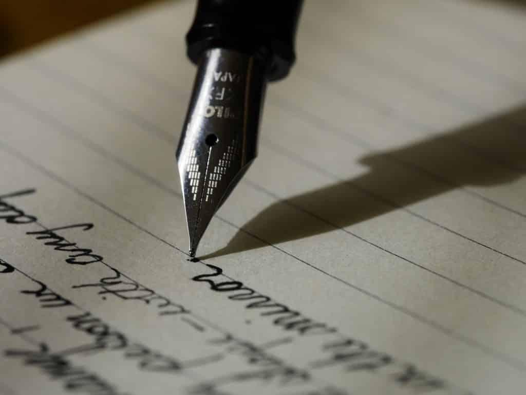 Pessoa escrevendo com caneta em um papel