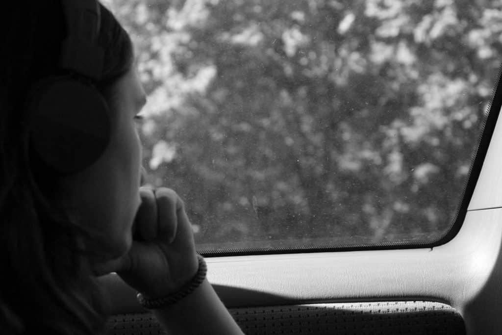 Mulher no banco de trás do carro olhando para a janela