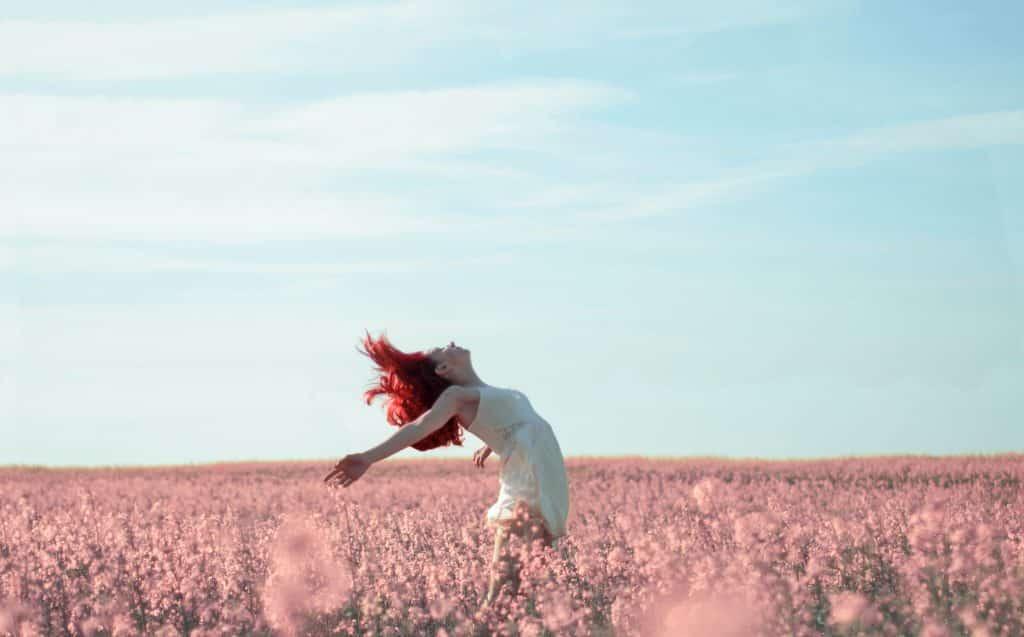 Mulher de braços abertos em um campo de flores
