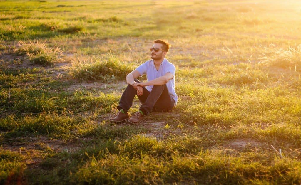 Homem sentado em um campo, na grama, durante o dia.