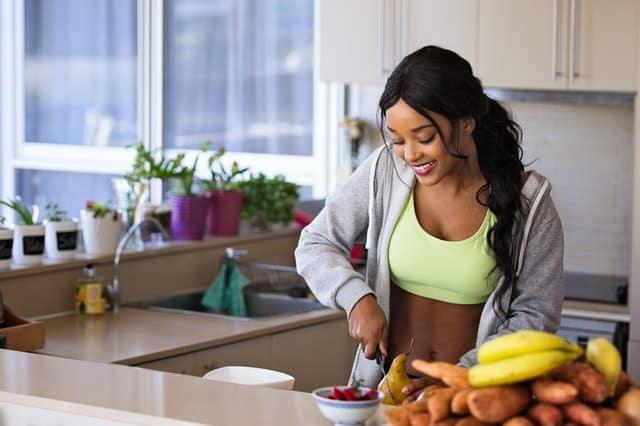 Mulher cortando fruta na cozinha