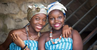 Imagem de duas amigas afrodescendentes. Elas estão alegres. Usam um corpete nas cores azul e branco e um turbante em suas cabeças, além de colares coloridos.