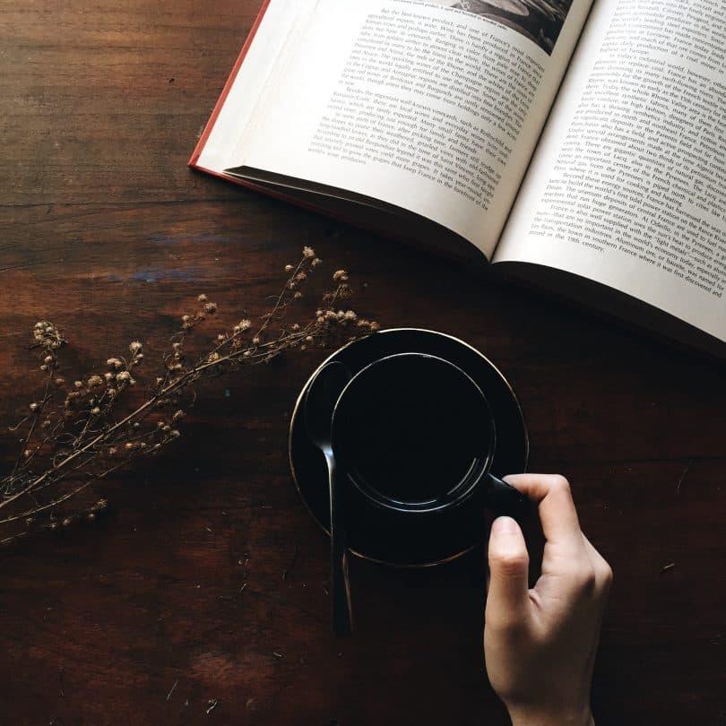 Mulher segurando xícara de chá ao lado de um livro aberto
