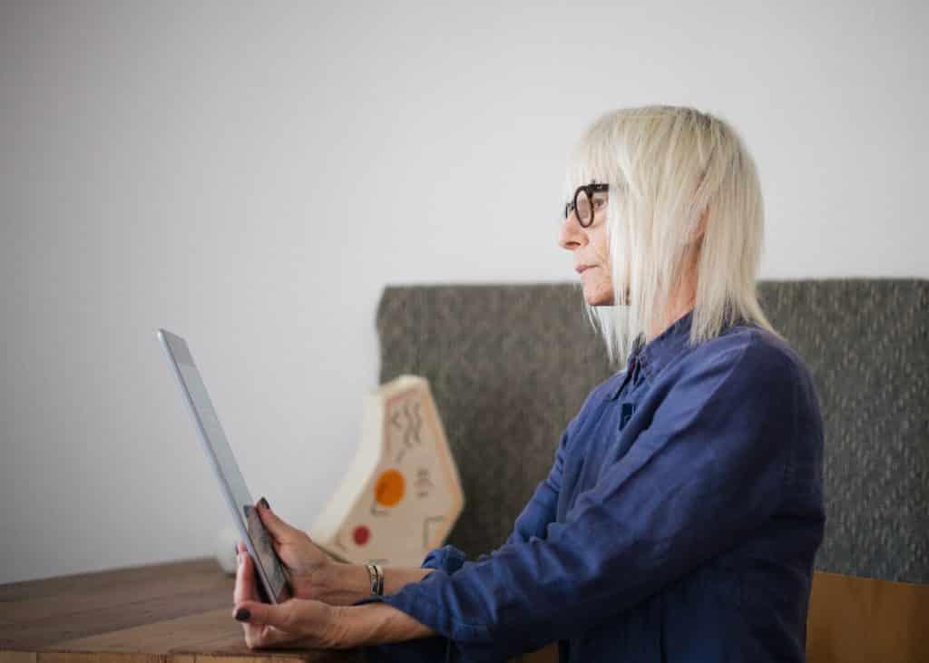 Idosa branca sentada usando um tablet.