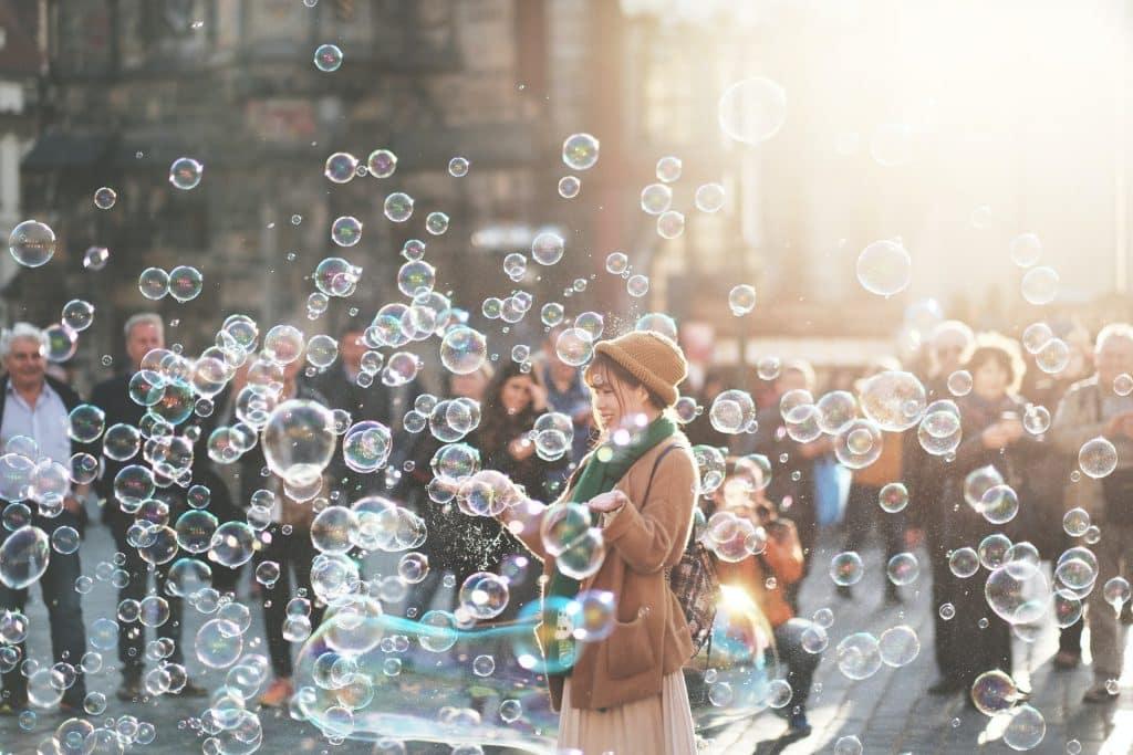 Mulher em um parque, em meio a bolhas de sabão.