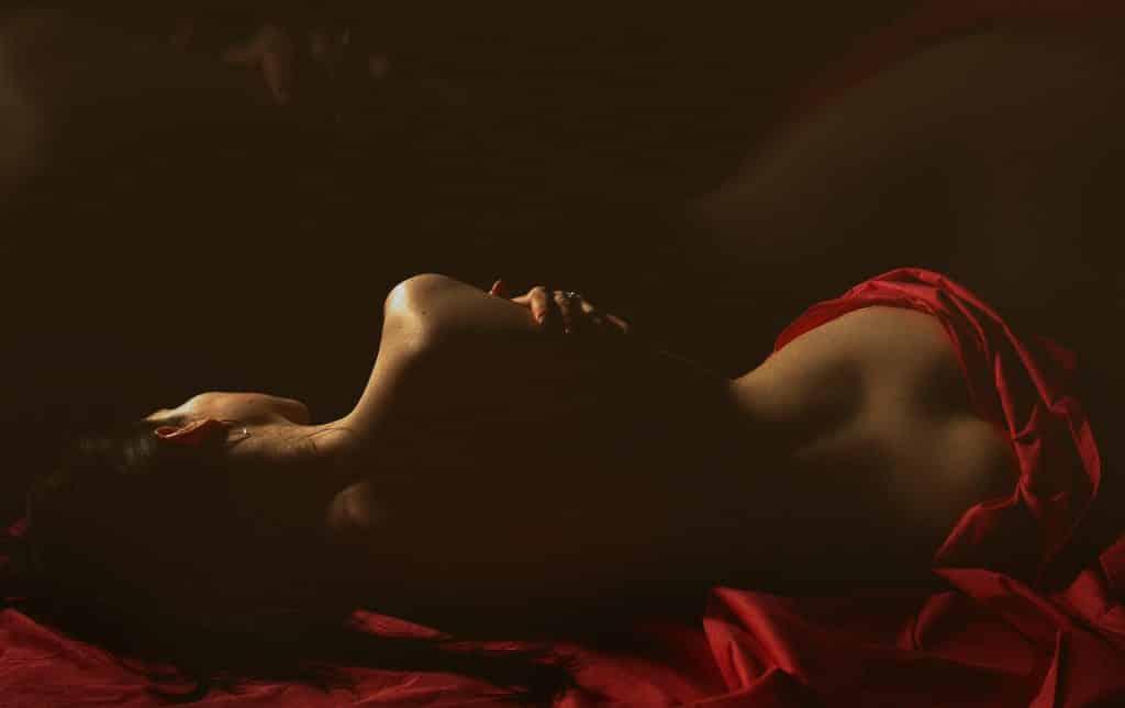 Mulher deitada de costas coberta por um lençol vermelho.