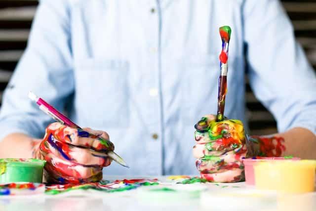 Homem com mãos sujas de tintas coloridas segurando caneta e pincel