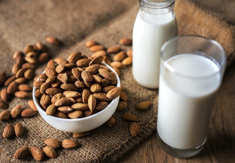 Pote com amêndoas ao lado de dois copos com seu leite, sobre uma mesa de madeira.