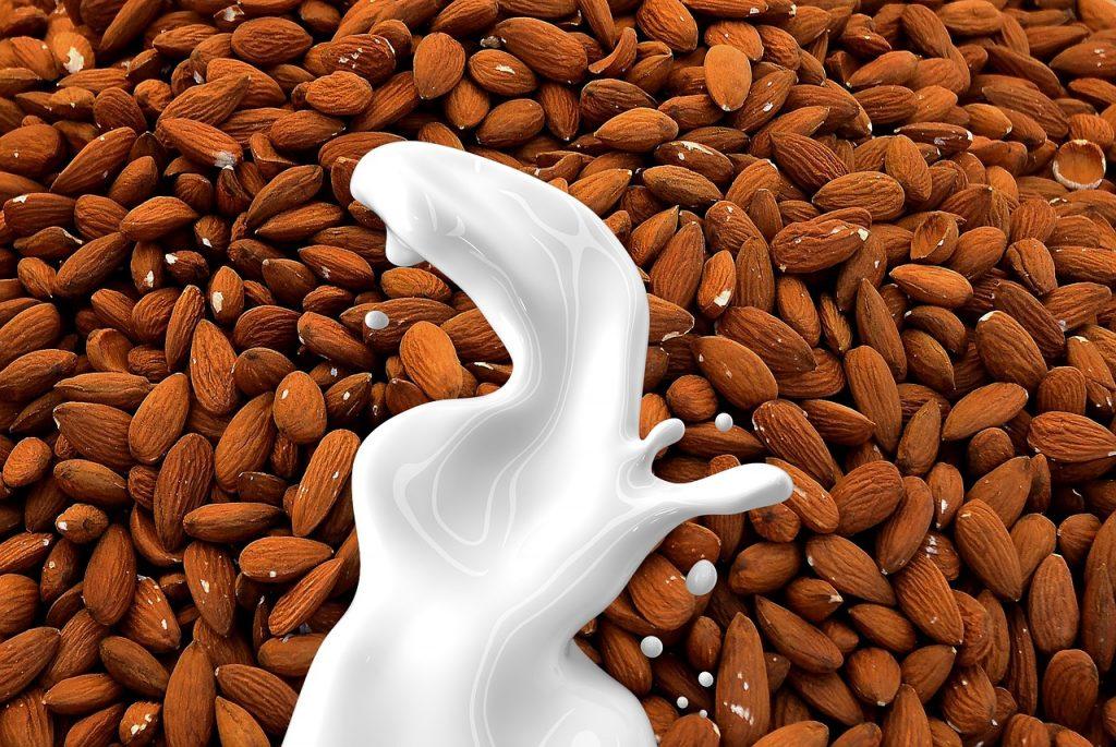 Ilustração de leite de amêndoas sendo derramado sobre amêndoas amontoadas.