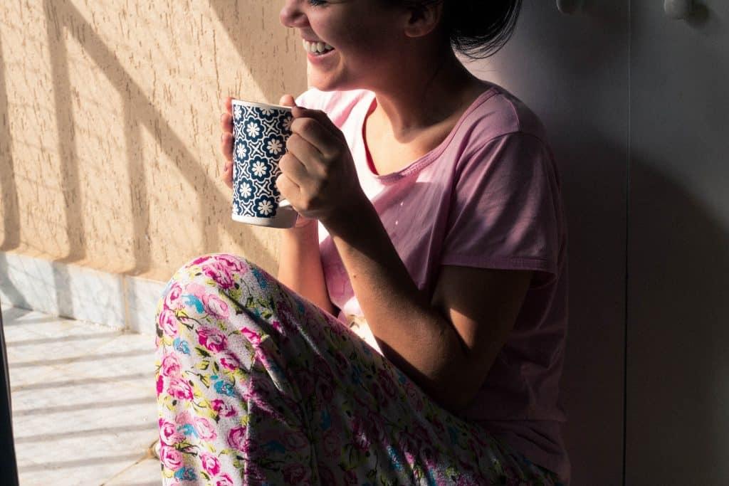 Mulher sentada na cama olhando para o lado sorrindo e segurando sua xícara