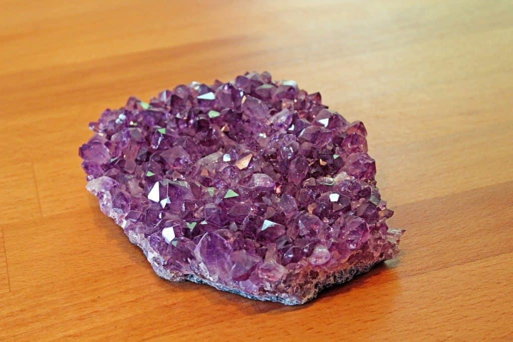 Imagem de uma linda e grande pedra ametista sobre uma mesa de madeira.