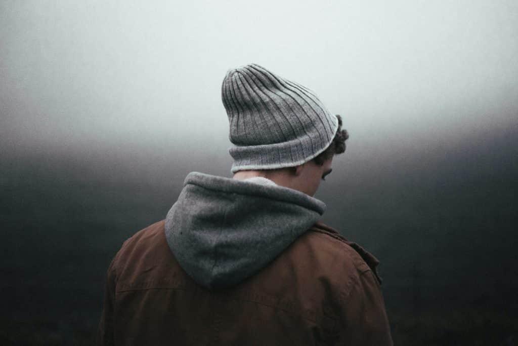 Homem usando jaqueta e touca olhando para o lado