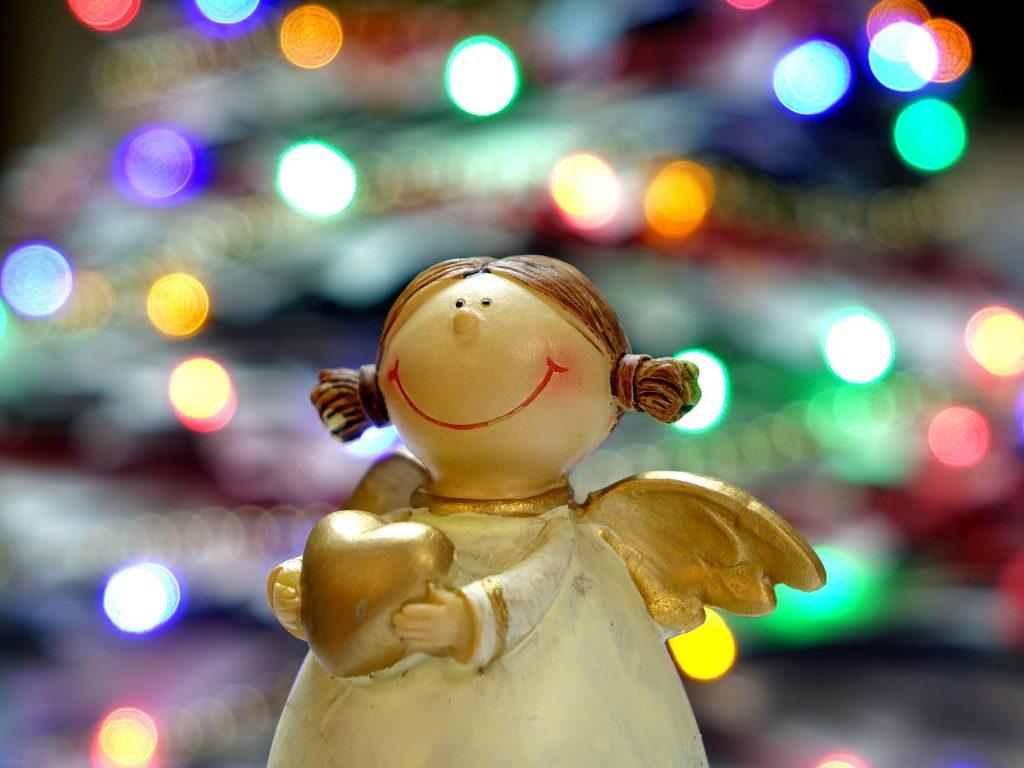 Imagem de um lindo anjinho natalino feito em  gesso pintado na cor branco. Suas asas são douradas. Ele segura entre as mãos um coração dourado.
