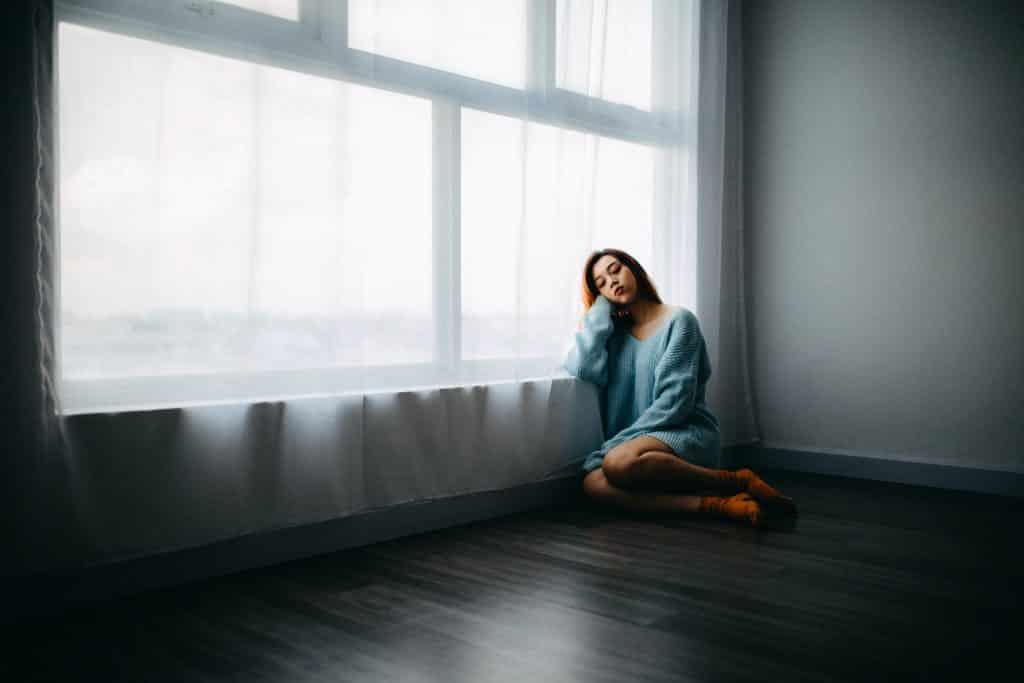 Mulher sentada no chão de sua casa ao lado de uma jenela com cortinas