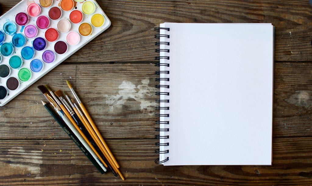 Caderno com pinceis e uma cartela de tinta aquarela ao lado.