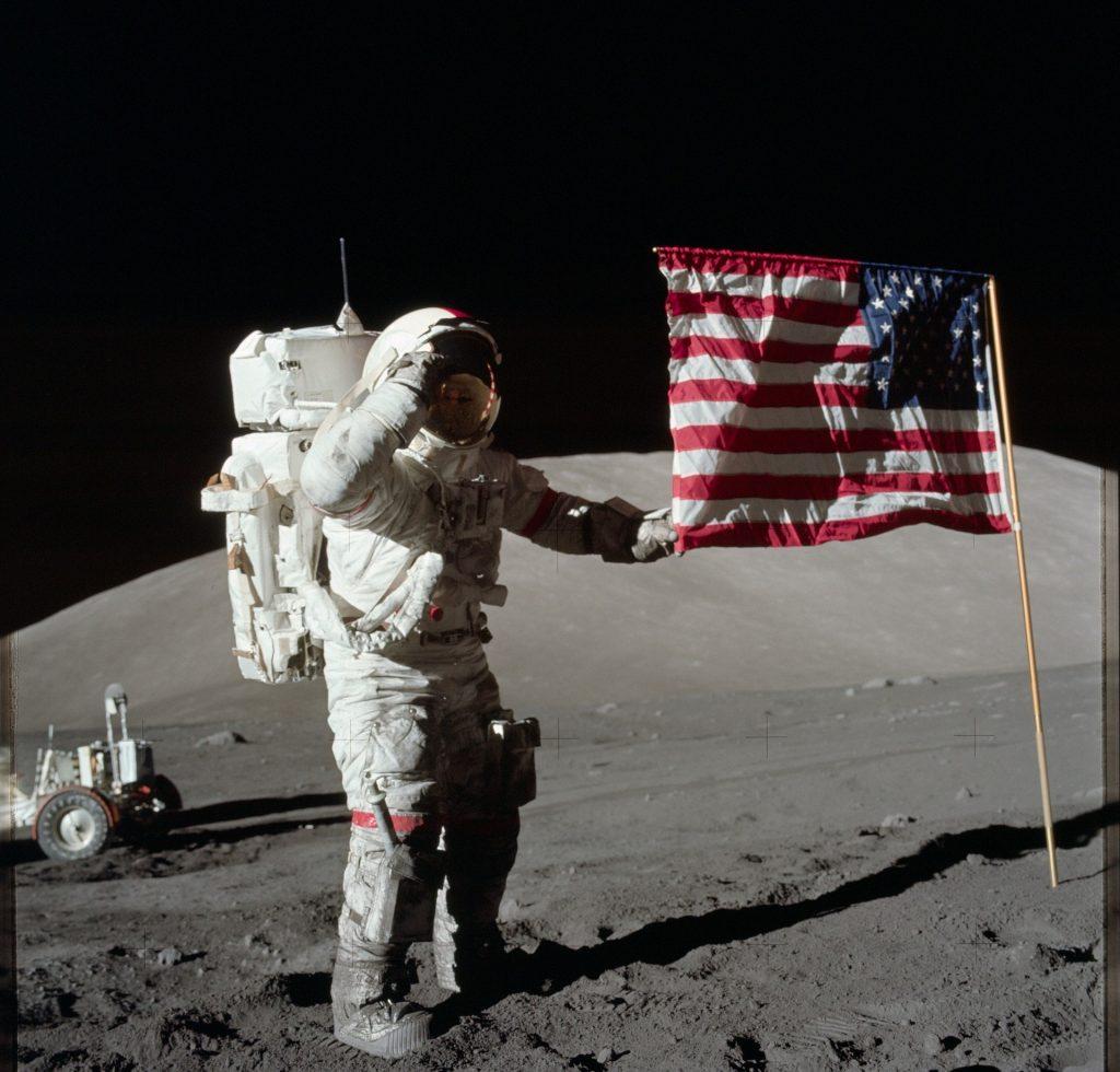Imagem do primeiro homem astronauta pisando sobre a lua. Ao lado dela a bandeira dos Estados Unidos.