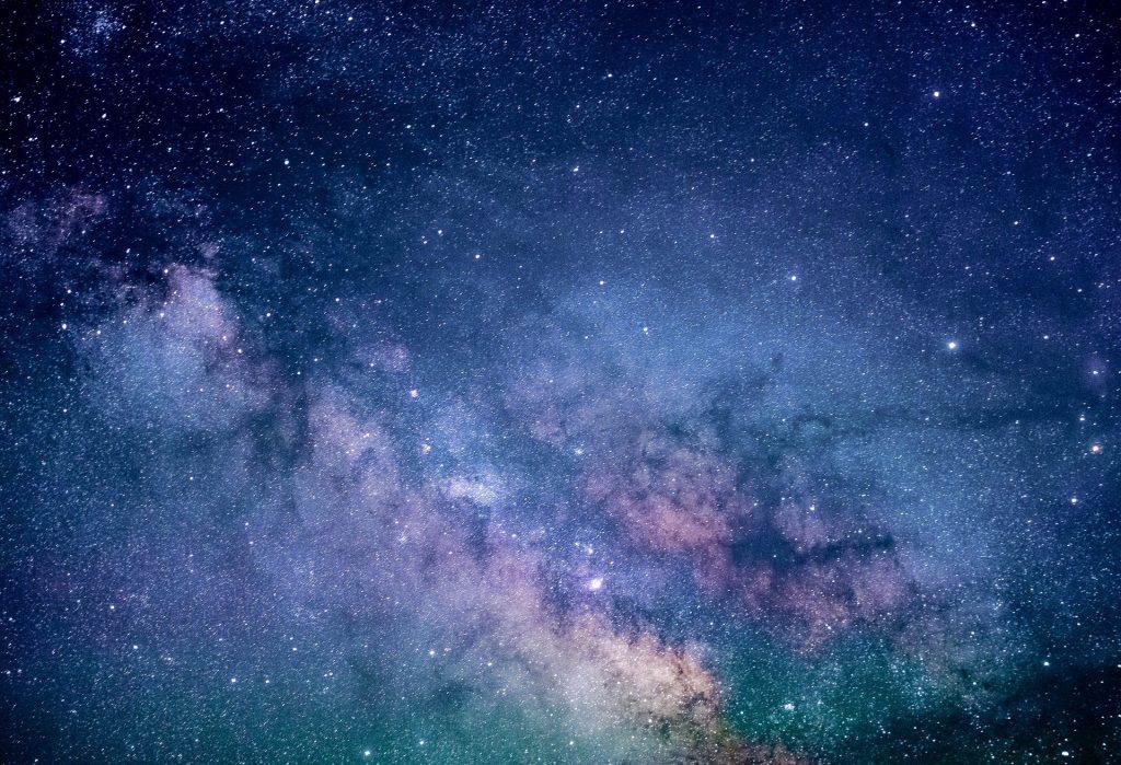 Imagem azulada e brilhante do universo com as estrelas em destaque.