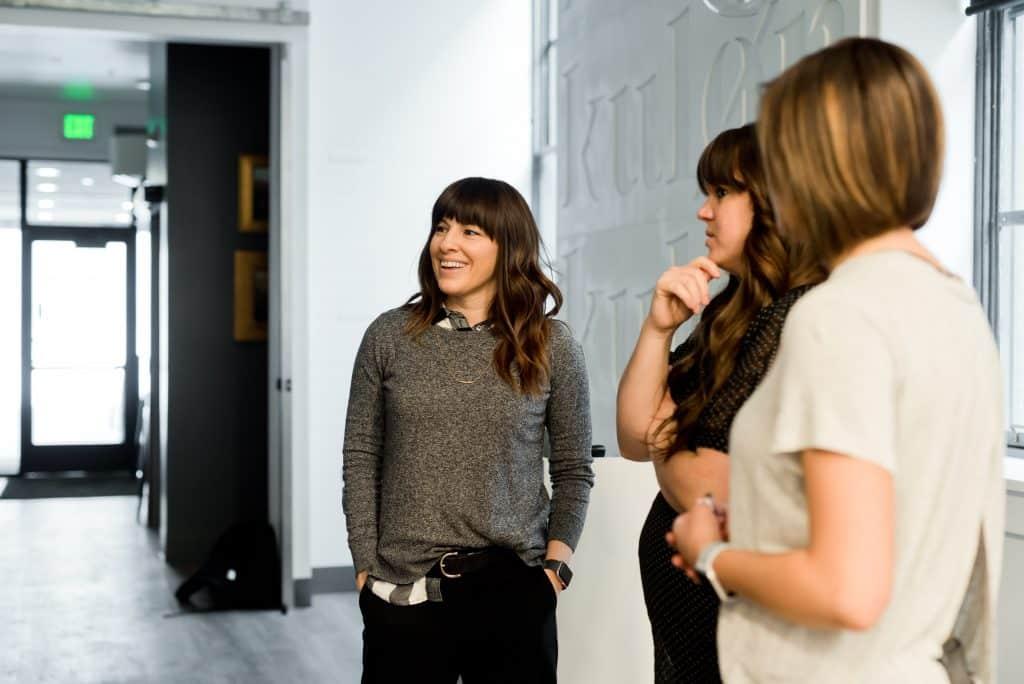 Três mulheres em pé, conversando, enquanto uma coloca a mão sobre o queixo e olha para o lado em sinal de julgamento.