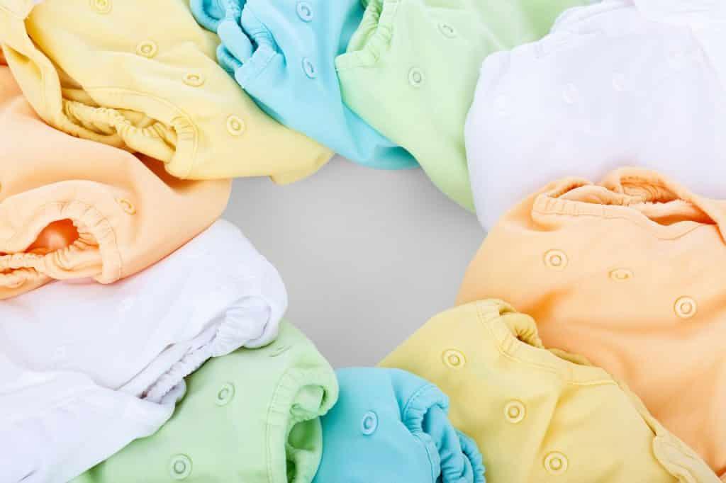 Imagem de fraldas ecológica de várias cores como: branca, amarela, laranja, verde e azul.