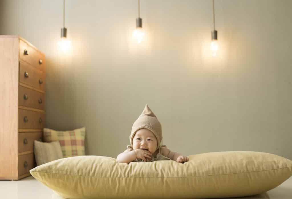 Imagem de um lindo bebê masculino oriental deitado de bruço sobre um grande almofadão disposto no chão do seu quarto.