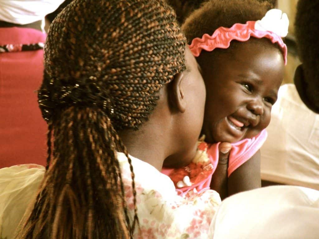 Linda bebê africana no colo de sua mãe. Ela está sorrindo.