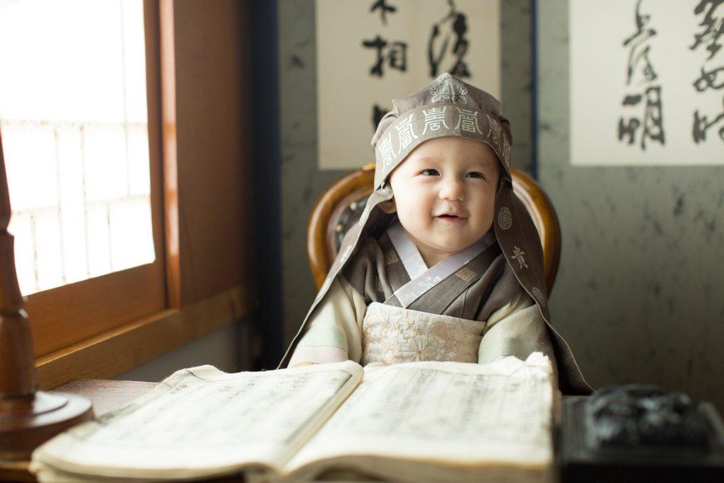 Imagem de um bebê coreado, usando uma roupa da cultura sentado em uma cadeirinha.