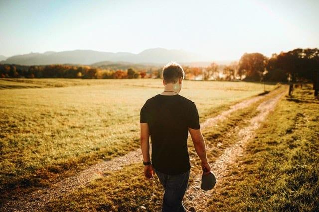 Homem caminhando de costas em estrada de terra e mato