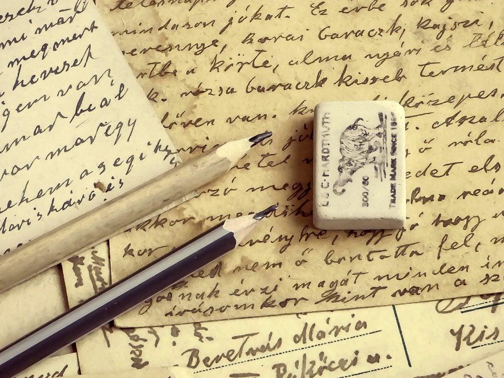 Imagem de um manuscrito antigo trazendo os resultados da missão Kepler. Ao lado dois lápis pretos e uma borracha.